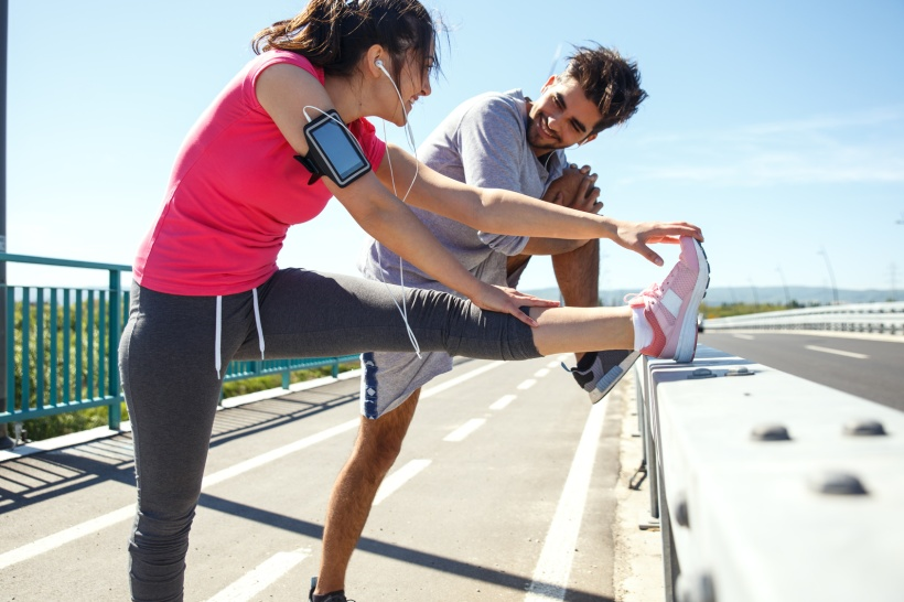 Young couple exercising and stretching muscles before jogging.